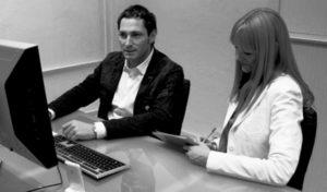 Usability-Test-Beispiel mit zwei Menschen nebeneinander an einem Schreibtisch vor einem PC sitzen. Usability Expertin Britta Litzenberg macht Notizen von dem was der Proband sagt,von Userfriend Usability Agentur, auf userfriend.de