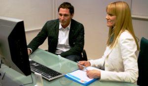 Usability-Test-Beispiel mit zwei Menschen nebeneinander an einem Schreibtisch vor einem PC sitzen. Usability Expertin Britta Litzenberg beobachtet und hört zu, was der Proband sagt, von Userfriend Usability Agentur, auf userfriend.de