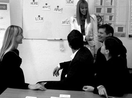 Fünf Menschen bei Userfriend in Aktion im Büro. Eine an einem Board stehend, vier andere davor am Tisch sitzend. Als Beispiel für UX Consulting und User Research im UX Design von Userfriend Usability Agentur, auf userfriend.de