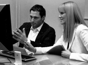Usability-Test-Beispiel, mit einem Mann und einer Frau, nebeneinander an einem Schreibtisch vor einem PC sitzen. Usability Expertin Britta Litzenberg fragt nach der Beobachtung den Probanden. Von Userfriend Usability Agentur, auf userfriend.de