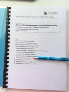 Ein Foto vom Qualitätsstandard für Usability Engineering und einem Stift mit der Aufschrift Userfriend, der mit anderen Namen von Autoren auf den Listen Punkt Litzenberg, Britta (userfriend.de) zeigt