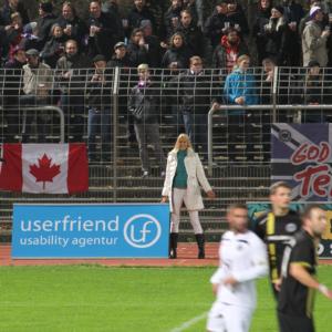 Ein Foto bei einem Fußballspiel in Berlin abgebildet sind: drei Fußballspieler und viele Zuschauer im Hintergrund mit einem Userfriend usability agentur Banner & Britta Litzenberg an der Seite des Spielfeldes für userfriend.de