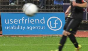 Das Logo von Userfriend-in großem realen Banner an der Seite des Spielfeldes, bei einem Fußballspiel in Berlin und ein Ball fliegt davor mit einem Fußballspieler angeschnitten, von Userfriend Usability Agentur, auf userfriend.de