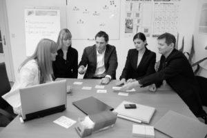 Fünf Menschen, davon UX Design Experten im Team, an einem Tisch sitzend bei der UX Konzeption in einer cardsorting test Darstellung (Sortieren von Navigation Menü Karten) von Userfriend Usability Agentur, auf userfriend.de