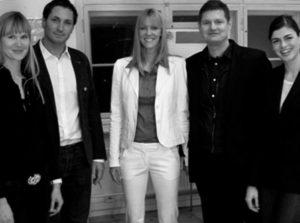 Fünf Menschen bei Userfriend. Drei Frauen und zwei Männer (abwechselnd, in der Mitte Britta Litzenberg) stehend, lachend, als freundliche Begrüßung in einem Usability Team bei userfriend.de