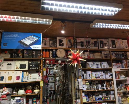 Ein Foto von einem realen Geschäftseingang, mit Blick auf die mit vielen verschiedenen Produkten gefüllten Regale vorne, einen Gang nach hinten weiterführend ins Lager ist erkennbar und eine Uhr, 5 vor 12, als Beispiel- es ist Zeit für UX
