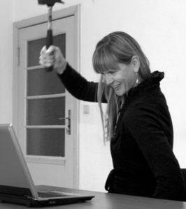 Ein Foto von einer Frau, an einem Tisch sitzend, vor einem offenen Laptop, mit einem Hammer in der rechten Hand und erhobenen Arm, aber lachend
