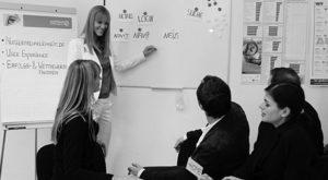 Ein Foto von fünf Menschen, davon ein UX Design Experten im Team, im Usability Workshop vor einer Tafel stehend bei der UX Konzeption, von Userfriend Usability Agentur, auf userfriend.de